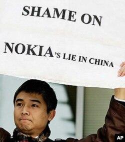 """益仁平中心负责人陆军, 2008年11月23日,陆军在诺基亚总部门前高举""""诺基亚在中 国的撒谎行为可耻""""的标语牌,抗议其乙肝歧视。"""