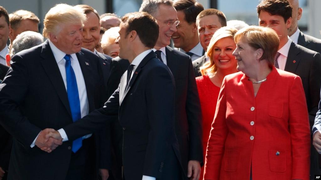 TT Mỹ Donald Trump bắt tay TT Pháp Emmanuel Macron, bên phải là Thủ tướng Đức Angela Merkel, tại Brussells, ngày 11/7/2018.