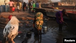 A women, right, displaced by the fighting in Bor county washes herself as another washes kettles, in the village of Mingkamen, in South Sudan, Jan. 14, 2014.