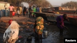 A women displaced by fighting in Bor county washes herself as another washes kettles in the village of Mingkamen on Jan. 14, 2014.