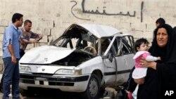 Warga mengamati sebuah mobil yang hancur di wilayah Zayona, sebelah Timur Baghdad (20/3). Dua orang tewas dan empat orang lainnya dilaporkan terluka dalam insiden yang bertepatan dengan peringatan 10 tahun invasi AS di Irak ini.