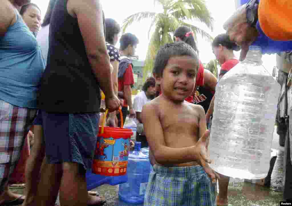 A boy fills a plastic bottle with water in Tacloban city, central Philippines, Nov. 11, 2013.