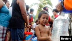 Filipinski dečak puni bosu pijaćom vodom na jednom od punktova za raspodelu himanitarne pomoći u teško pogođenom području Filipina