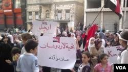 Niños y mujeres sirios pueden ser vistos en la foto tomada por ciudadanos con teléfonos celulares, con carteles donde reclaman la salida de al-Assad del poder.