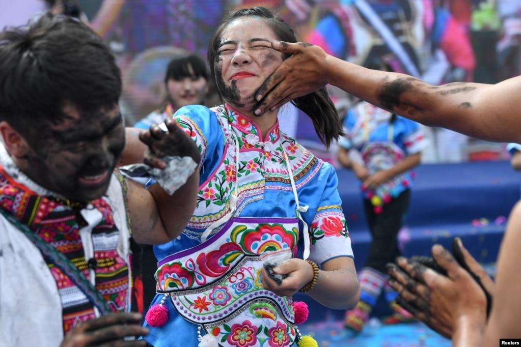 在云南丘北县的彝族传统节日,人们互相在脸上抹灰,以表示祝你好运。(2017年7月18日)