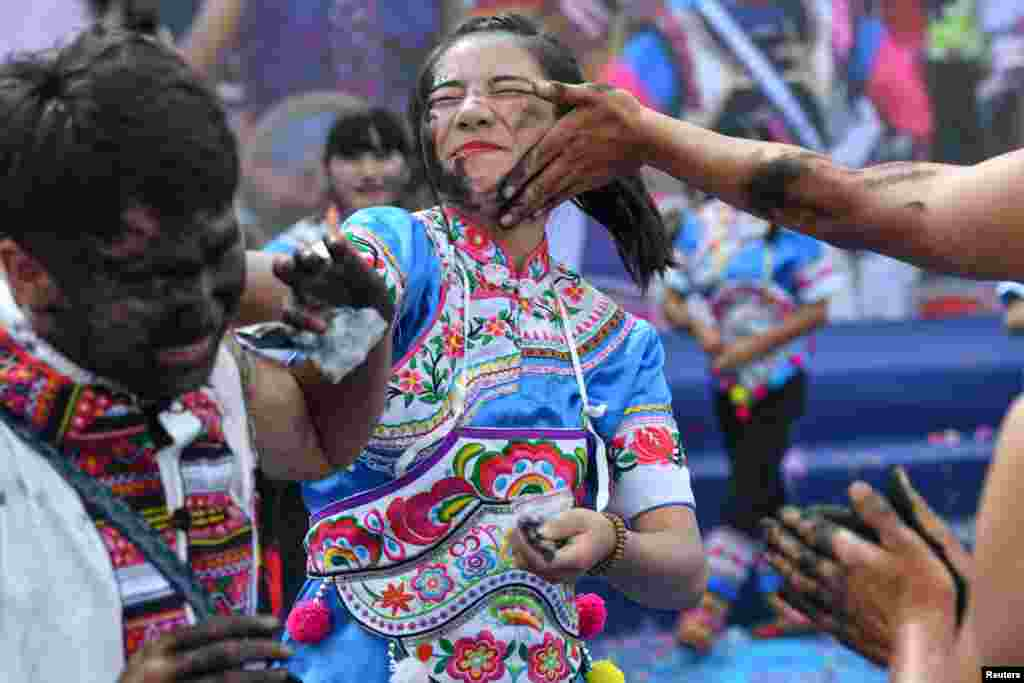 People smear black ash with hands onto each other to wish for good luck and fortune during a traditional festival of the Yi ethnic minority in Qiubei County, Yunnan province, China.