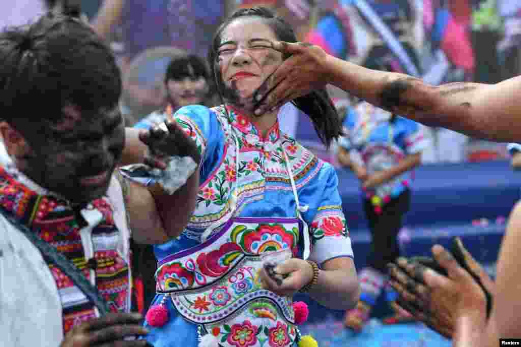 Warga mengusapkan abu arang hitam ke wajah orang lain dalam festival tradisional untuk mendoakan keberuntungan, tradisi etnis minoritas Yi di kota Qiubei, Yunnan, China.