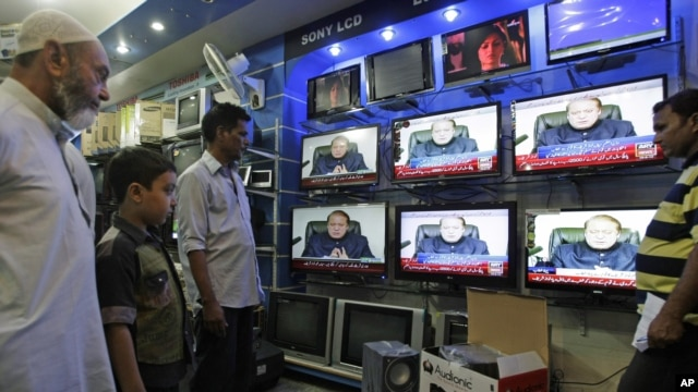 People watch Prime Minister of Pakistan Nawaz Sharif addressing the nation, at an electronic shop in Karachi,  Aug. 19, 2013.