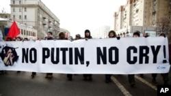 图为抗议者2月4日抬着反普京标语在莫斯科市中心游行