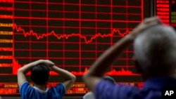 Investors monitor a display showing the Shanghai Composite Index at a brokerage in Beijing, Aug. 31, 2015.