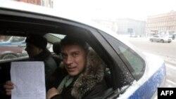 Борис Немцов в милицейской машине с протоколом решения суда об аресте. 2 января 2011г.
