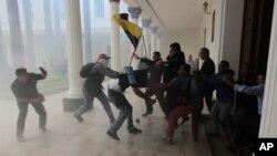 Законодатели-оппозиционеры участвуют в потасовке проправительственными активистами, когда те пытаются прорваться вздание парламента страны. Каракас. Венесуэла. 5 июля 2017 г.