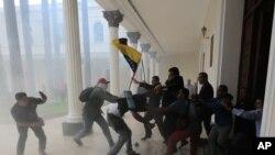 Militan kap defann gouvènman Nicolas Maduro a kap eseye pran daso, lokal palman an ki anba kontwòl opozisyon an. Karakas, Venezuela, Mèkredi 5 jiyè 2017. (Foto: AP/Fernando Llano)