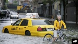 A bicyclist makes his way past a stranded taxi on a flooded New York City Street as Tropical Storm Irene passes through the city, August 28, 2011. A global warming-fueled sea level rise over the next century could flood millions in the US, according to a