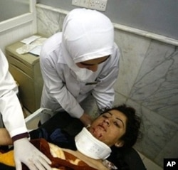 FILE - A wounded Iraqi woman receives medical care at a hospital in the northern Iraqi city of Mosul, after a double bomb attack targeting buses carrying Christian students and university workers near Mosul in killed a shopkeeper and wounded 80 other people in April 2012. 02