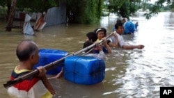 Residents wade through flood water by holding a float-attached pole as they evacuate their homes in Nakhon Ratchasima province, northeastern Thailand, 17 Oct 2010
