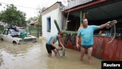 Local residents stand in a flooded courtyard of a house in the town of Krymsk, which has been seriously damaged by floods, in the Krasnodar region, southern Russia, July 8, 2012.