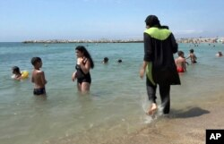 FILE - In this Aug. 4, 2016 file photo made from video, Nissrine Samali, 20, gets into the sea wearing a burkini, a wetsuit-like garment that also covers the head, in Marseille, France.