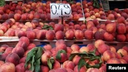 Peaches are displayed on a fruit vendor's stall at a grocery market in Athens, Greece, Aug. 8, 2014.