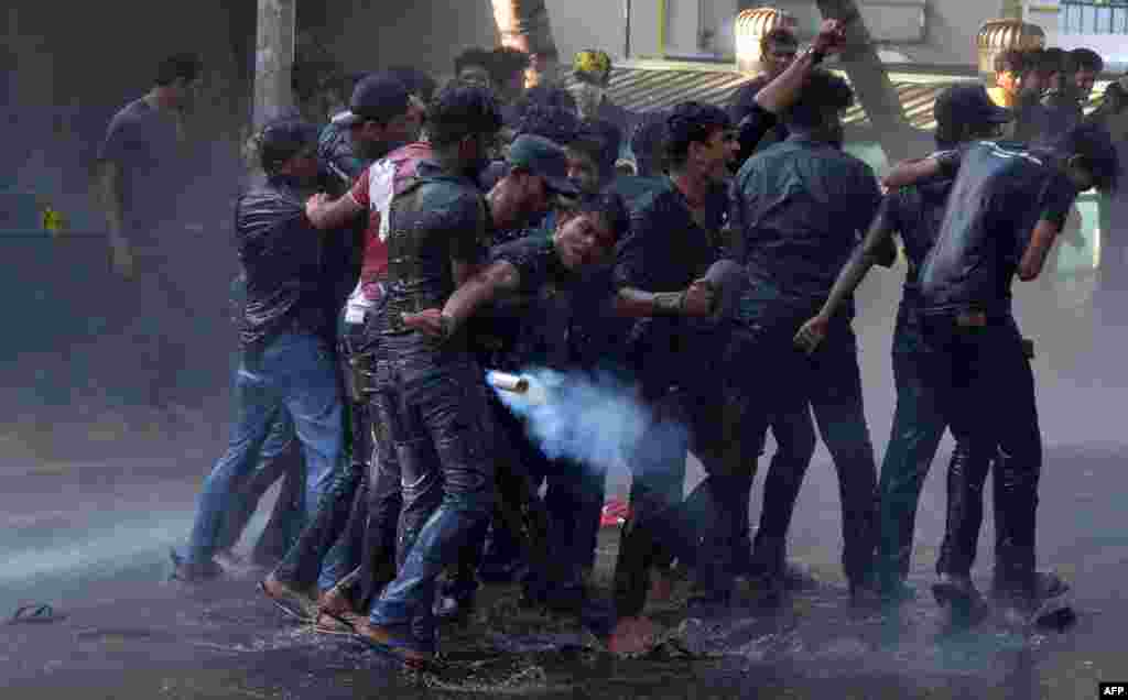 A Sri Lankan Higher National Diploma student throws a tear gas canister back towards the police during clashes in a protest march demanding better conditions at state-run universities, in Colombo.
