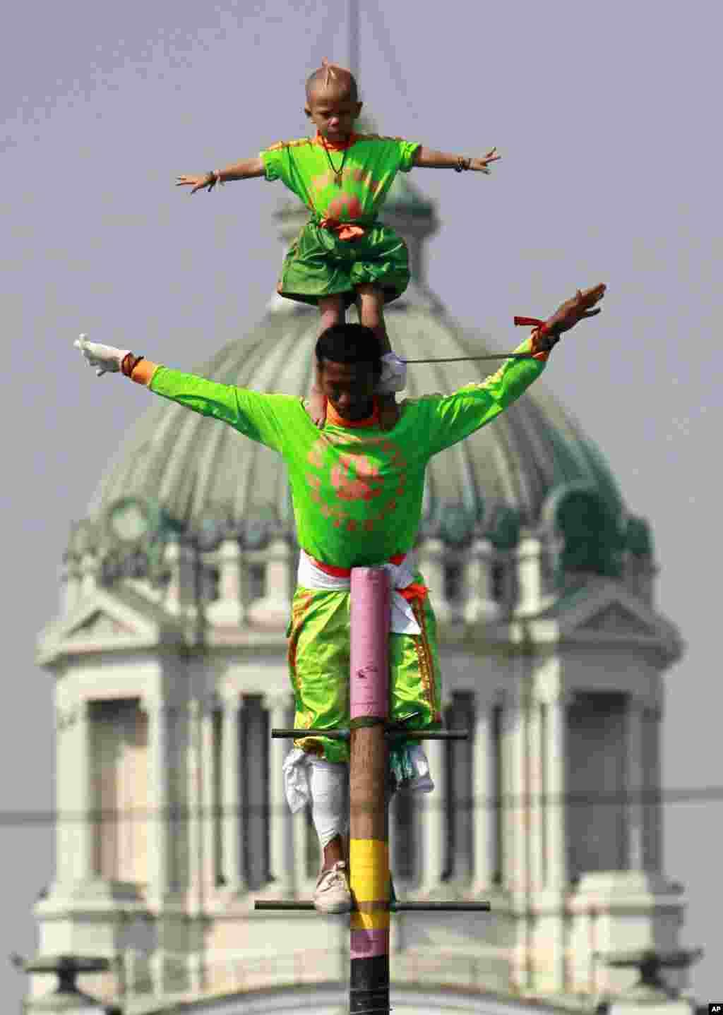 Dua anak laki-laki Thailand melakukan pertunjukan akrobat untuk menghibur para demonstran anti-pemerintah di kawasan Royal Plaza, Bangkok, Thailand.