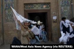 Seorang pendukung Taliban membawa bendera Taliban di sebuah masjid di Herat, Afghanistan, 10 September 2021. (Foto: WANA/West Asia News Agency via REUTERS)