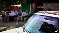 Para pendukung presiden Mesir yang terguling, Mohammed Morsi, melancarkan aksi duduk di dekat mobil yang rusak akibat bentrokan dengan polisi di daerah kampus Universitas Kairo, Giza, Mesir (23/7).