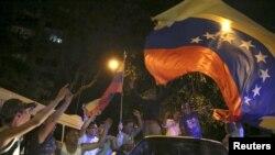 Para pendukung oposisi koalisi Partai Persatuan Demokratik Venezuela merayakan kemenangan mereka dengan melambaikan bendera Venezuela di jalanan kota Caracas (7/12).
