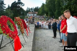 FILE - From left, Norway's Prime Minister Erna Solberg, Labor Party leader Jonas Gahr Stoere, National Support Group's leader Trond Henry Blattmann and leader of Labor Youth of Norway (AUF) Eskil Pedersen lay wreaths on Utoya Island, July 22, 2014.