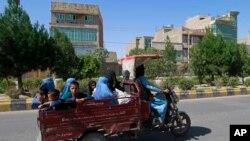 اس ماہ کے آغاز پر افغان خواتین اور بچے صوبہ ہرات میں لڑائی کے دوران ایک موٹر سائکل گاڑی پر سوار سفر کر رہے ہیں، فوٹو اے پی
