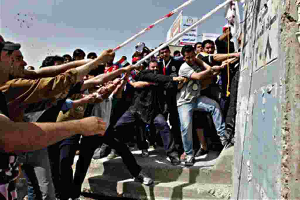Iraqi anti-government protesters pull concrete blast walls leading to the heavily guarded Green Zone during a demonstration in Baghdad, Iraq, Friday, Feb. 25, 2011. Thousands marched on government buildings and clashed with security forces in cities acros