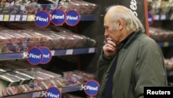Seorang calon pembeli melihat daging yang dijual di supermarket Tesko di Stortford, Inggris . Konsumen di Eropa dicemaskan oleh berita terkontaminasinya daging sapi dengan kuda.