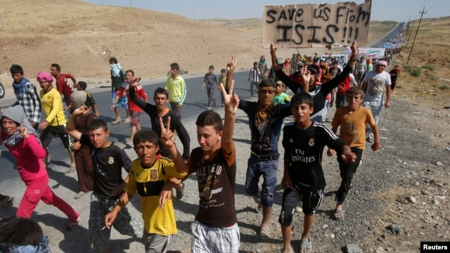 Displaced people from the minority Yazidi sect, who fled the violence in the Iraqi town of Sinjar, flash signs as they take part in a demonstration at the Iraqi-Syrian border crossing in Fishkhabour, Dohuk province, August 13, 2014.