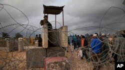 Trabajadores palestinos cruzan una sección de un muro de separación entre el asentamiento judío de Modiin Élite y el pueblo cisjordano de Harbeta para volver a casa después de la jornada de trabajo en Israel.