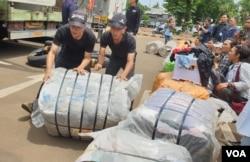 Petugas menurunkan bungkusan-bungkusan pakaian yang disita bea cukai dan diduga akan dikirim ke Bandung untuk dijual kembali, 11 Maret 2020. (Foto: Rio Tuasikal/VOA)