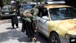 Chiến binh Taliban lục soát xe qua lại tại một điểm kiểm soát trên đường đến Kabul, Afghanistan, ngày 22/8/2021.