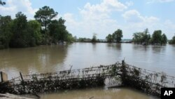 FILE - A barbed-wire fence encircles the Highlands Acid Pit that was flooded by water from the nearby San Jacinto River as a result from Harvey in Highlands, Texas, Aug. 31, 2017.