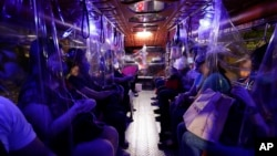 Plastic sheets on a traditional Jeepney bus separate passengers as part of health measures to help prevent the spread of the new coronavirus in metropolitan Manila, Philippines.
