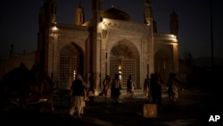 Taliban fighters walk at the entrance of the Eidgah Mosque after an explosion in Kabul, Afghanistan, Oct. 3, 2021.