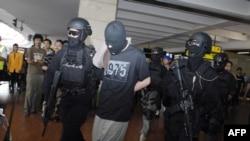Pasukan anti-teror Densus 88 membawa empat warga asing yang ditangkap di Sulawesi, di bandar udara Jakarta (14/9). (AFP/Bima Sakti)