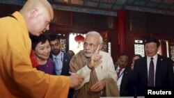 Indian Prime Minister Narendra Modi (C) gestures as he visits the Daxingshan Buddhist temple, in Xian, Shaanxi province, China, May 14, 2015.