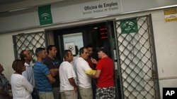 A man offers his queue ticket as people wait in line to enter a government job center in Marbella, Spain, September 2, 2011.