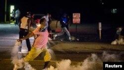 Namoyishchilar favqulodda holat e'lon qilinganiga qaramay, ko'chalarni tark etmayapti, Ferguson, 17-avgust, 2014-yil.