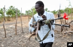 An opposition fighter walks with his weapon on which is tied a red ribbon, signifying danger as a warning to government forces and a willingness to shed blood, according to an opposition spokesman, in Akobo town, one of the last rebel-held strongholds in