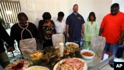 Rondy Bridges, third from right, leads a Thanksgiving Day prayer before he and members of his family have their holiday meal. (file)