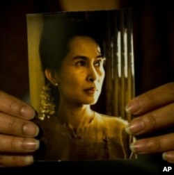 一缅甸妇女手持缅甸民主运动领袖昂山素季的照片