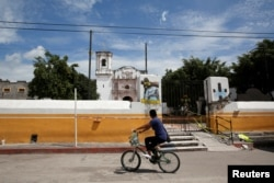 A man rides a bicycle past a church dome which collapsed in an earthquake is seen in Axochiapan, near Mexico City, Mexico September 29, 2017. REUTERS/Henry Romero