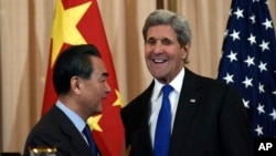 Secretary of State John Kerry talks with with Chinese Foreign Minister Wang Yi as they wrap up their news conference at the State Department in Washington, Feb. 23, 2016. (AP Photo/Susan Walsh)