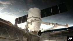 This frame grab made available by NASA TV shows a view of the SpaceX Dragon anchoring to the International Space Station, March 3, 2013.