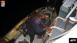 FILE - Refugees climbing aboard an Italian naval vessel near the Italian port of Pozzallo, south of Sicily.